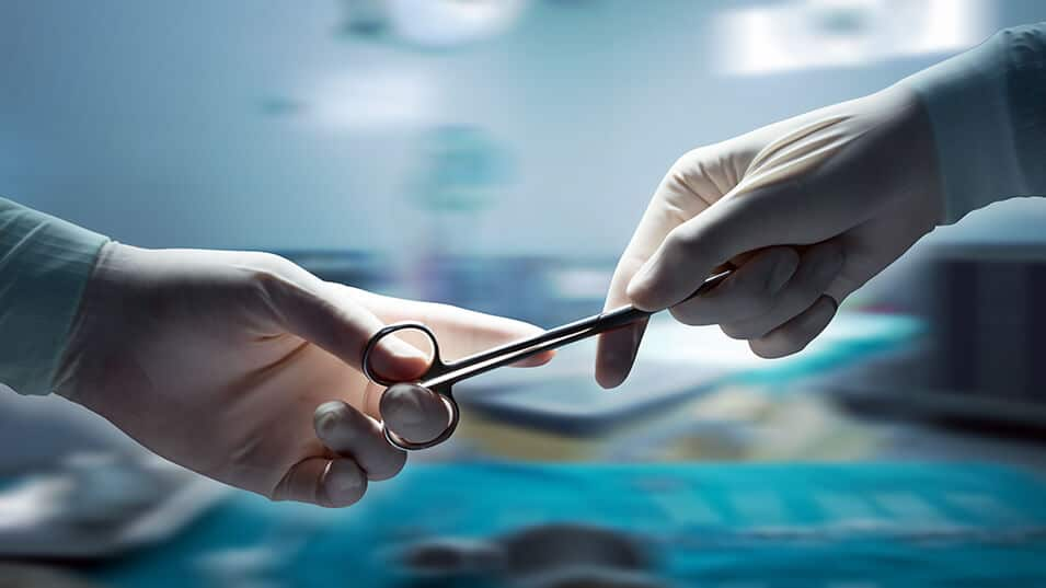 photograph of one hand surgeon passing forceps to another hand surgeon during surgery