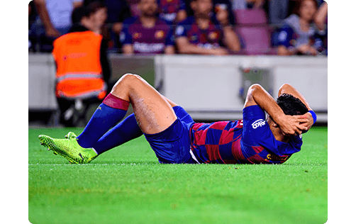 picture showing a barcelona football player lying injured on the ground with his hands behind his head